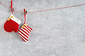 Christmas background. Red Christmas socks and mitten on gray background. Copy space.