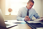 Mature businessman sitting at his desk looking through documents