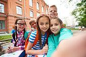 Jolly carefree school friends taking selfie