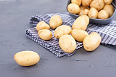 Young potatoes are clean in a cup and on a towel. Summer harvest. Vegetables and health, Copy space