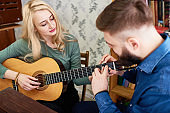 Man teaching girlfriend to play guitar