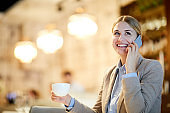 Smiling carefree beautiful businesswoman in jacket talking by mobile phone and drinking coffee in cafe