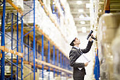 Inventory manager scanning boxes in warehouse