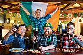 Patriotic Irish men celebrating Saint Patrick Day together at pub