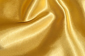Texture, fabric, background. Abstract background of luxurious fabric or liquid waves or wavy grunge crease silk satin texture of velvet material or luxurious Christmas or elegant background. gold