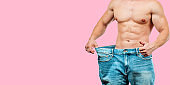 Man wearing big jeans after diet on pink background