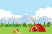 Camping in the mountains, tourist tent on the green grass