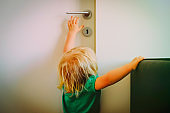kids safety - little girl try to reach door handle