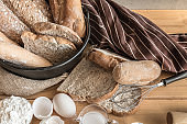 Male baker prepares bread. Male baker sprinkle the dough with flour. Making bread. Top view. Rustic style, Different kinds of bread rolls on table wooden from above. Kitchen or bakery poster design