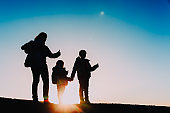 Silhouettes of mother with kids enjoy hiking at sunset