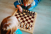 little boy and girl play chess, learning