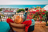 young man relax on balcony terrace with suitcase, travel concept