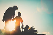silhouette of family with kids play at sunset beach