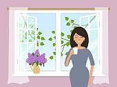 Young woman is drinking coffee by the open window