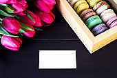 Box with macaroons and a bouquet of tulips and a card for your text on a dark background.
