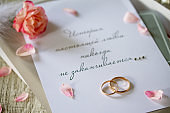 Two Golden Wedding Rings, box of chocolates and a wedding invitation, an inscription that the story of true love never ends, close-up.