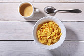 Corn Flakes cereal in a bowl and cap with espresso coffee. Morning breakfast.