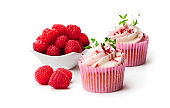 Chocolate  cupcakes with fresh raspberries and cream isolated on white