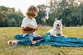 Little girl with white dog Husky in the park sits on the grass, plays, reads, resting