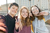 Portrait of three teen friends boy and two girls smiling and taking a selfie outdoors. City background, golden hour