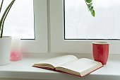Winter time, snow-covered window, an open book and a cup with a hot drink on the windowsill