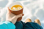 Outdoor winter time, womans hands with cup of coffee, background of snow