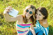 Mom and daughter teen together. Do selfie on the phone.