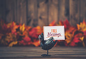 Autumn leaves with little crow holding message
