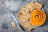 Pumpkin hummus seasoned with olive oil and black sesame seeds with whole grain crackers. Healthy vegetarian appetizer or snack