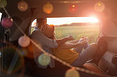 Young couple sitting in their car trunk and watching the sunset