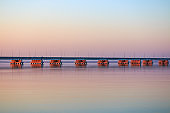 Low water bridge from Sedanka to the De Friz peninsula across the Amur Bay of Primorsky Krai Russia against the background of a red sunset sky.