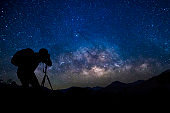 Photographer with starry night sky milkyway