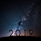 Silhouette of businessman on starry night sky. Freedom or victory concept of Happy New year 2019.
