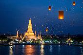Wat Arun temple on night in Bangkok city with yeepeng float lantern background