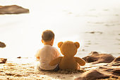 Baby and teddy bear sit togather on the beach, this immage can use for kid