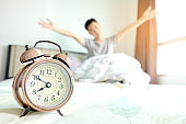 Morning of a new day, alarm clock wake up man in the room. A man stretch the muscles at window. Health care concepts