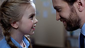 Smiling father and daughter looking at each other, family connection, trust