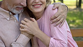 Loving senior couple embracing in park, comfortable retirement, secure old age