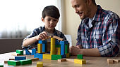 Handsome little boy and father playing colored toy cubes at home, childhood