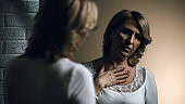 Depressed senior woman looking at reflection in mirror, skin cancer, worries