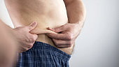 Man with beer belly looking at his folds, considering about dieting, body care