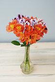 Spring Flowers Orange alstromeria flwoers in Glass Vase Wooden Background