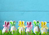 Easter funny bunny on green grass with easter eggs. Easter background.