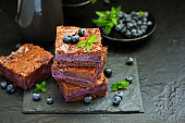 Chocolate brownies with blueberries and cream filling. Dark background.
