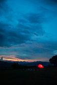 Illuminated camping tent at twilight under sunset sky on the mountain peak. Thai-Laos border. Phu Suan Sai National Park, Na Haeo, Loei, Thailand. Winter season. Silhouette. Noise, Grain. Outdoors adventure concept.