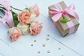 Lovely soft orange pink color rose tied by pink ribbon and brown gift box on white wood table background, sweet valentine present concept, copy space