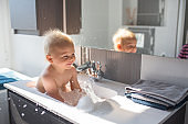 Baby taking bath in sink. Child playing with foam and soap bubbles in sunny bathroom with window. Little boy bathing. Water fun for kids. Hygiene and skin care for children