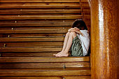 Sad child, sitting on a staircase in a big house, concept for bullying