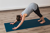 Pregnant woman doing prenatal yoga in downward facing dog posture