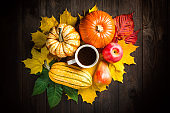 Autumn backdrop decoration with pumpkins, marrow, apple, pear, cup of coffee and colorful leaves on dark wooden background. Top view